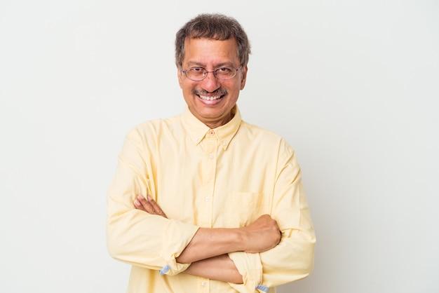 Indischer mann mittleren alters isoliert auf weißem hintergrund, der sich selbstbewusst fühlt und die arme mit entschlossenheit kreuzt.