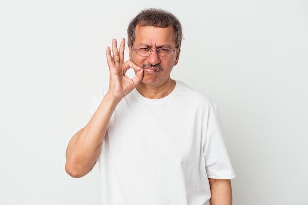 Indischer mann mittleren alters isoliert auf weißem hintergrund mit den fingern auf den lippen, die ein geheimnis bewahren.