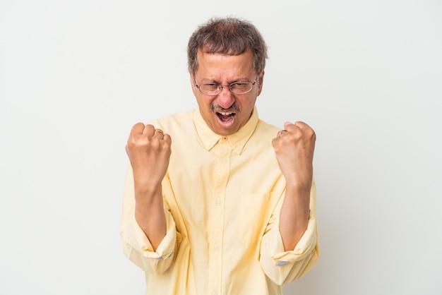 Indischer mann mittleren alters isoliert auf weißem hintergrund verärgert schreiend mit angespannten händen.
