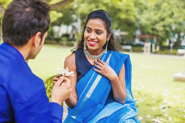 Indischer mann schenkt seiner verlobten franjipani-blumen
