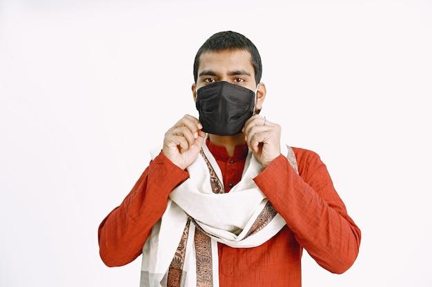 Indischer mann setzt auf medizinische maske mann in orange hemd und schal zeigt, wie man medizinische maske aufsetzt.