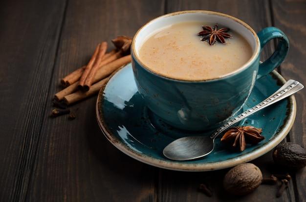 Indischer masala chai tee. gewürztee mit milch auf dunklem holz.