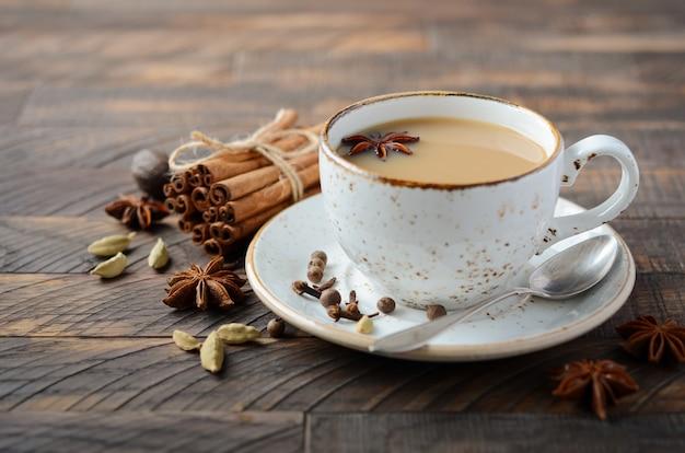 Indischer masala chai tee. gewürztee mit milch auf dunklem holz