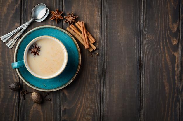 Indischer masala chai tee. gewürztee mit milch auf dunklem holztisch. draufsicht, flache lage, kopienraum.