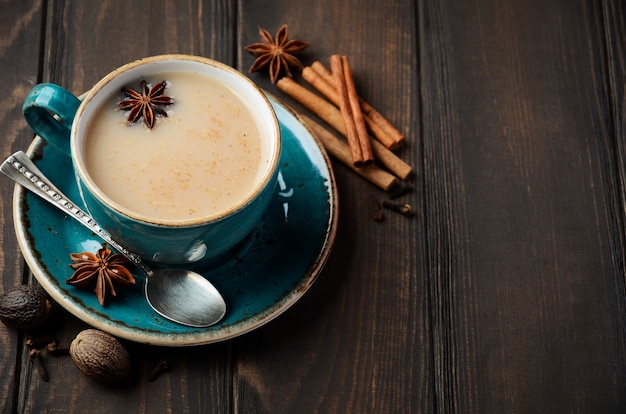 Indischer masala chai tee. gewürztee mit milch auf dunklem holztisch.