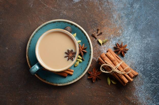 Indischer masala chai tee. gewürztee mit milch auf dunkler rostiger draufsicht, flache lage.