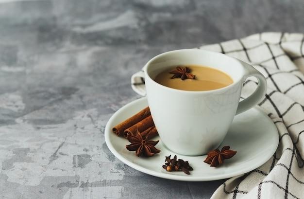 Indischer masala chai tee gewürztee mit milch auf grauem betonhintergrund