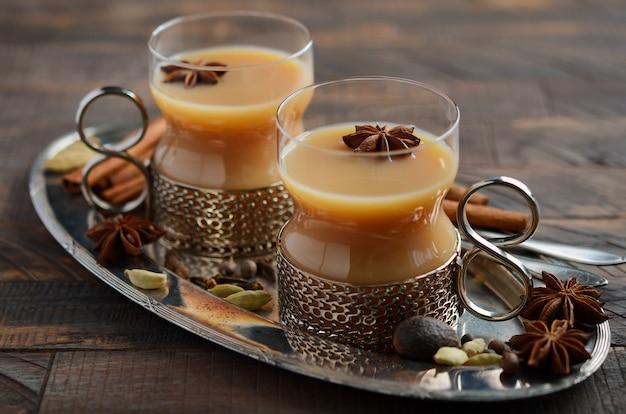 Indischer masala chai tee. gewürztee mit milch in den weinleseschalen auf dem rustikalen holztisch.