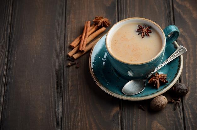 Indischer masala-chai-tee. gewürzter tee mit milch auf dem dunklen holztisch.