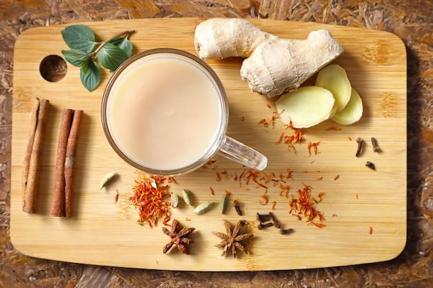 Indischer masala tee. belebender tee mit gewürzen, zutaten auf dem brett. draufsicht.