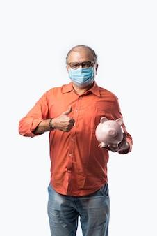 Indischer pensionierter älterer mann, der ein sparschwein oder eine spardose hält, während er bei einer pandemie eine gesichtsmaske trägt