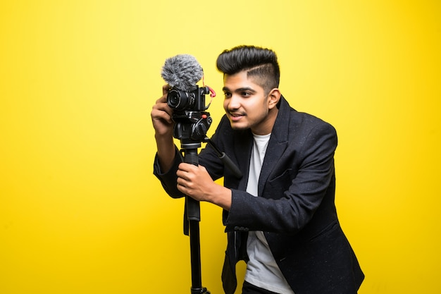 Indischer professioneller kameramann, der ereignis mit einem video abdeckt, das auf gelbem hintergrund isoliert wird