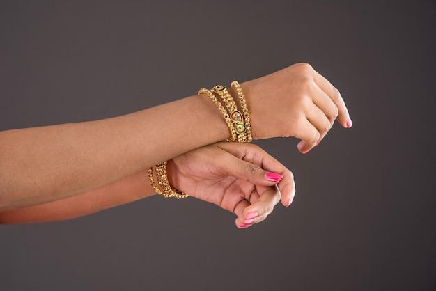Indischer schmuck - nahaufnahme eines mädchens, das traditionelle designer-goldarmreifen oder -armbänder trägt und anmutige tanzposen der hand auf dunklem hintergrund zeigt, selektiver fokus