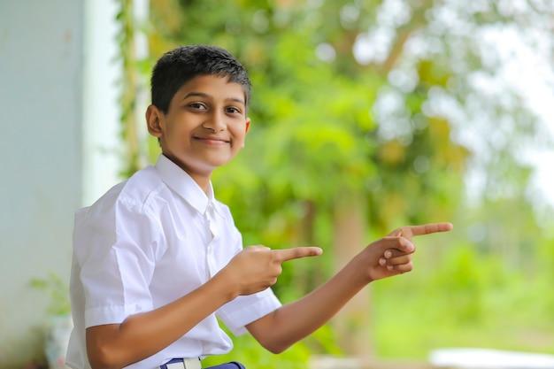 Indischer schuljunge, der richtung mit der hand zeigt