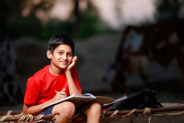 Indischer schuljunge mit notizbuch und lernen zu hause