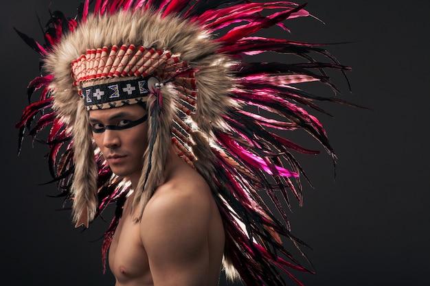 Indischer starker mann mit traditionellem amerikanischem ureinwohner bilden