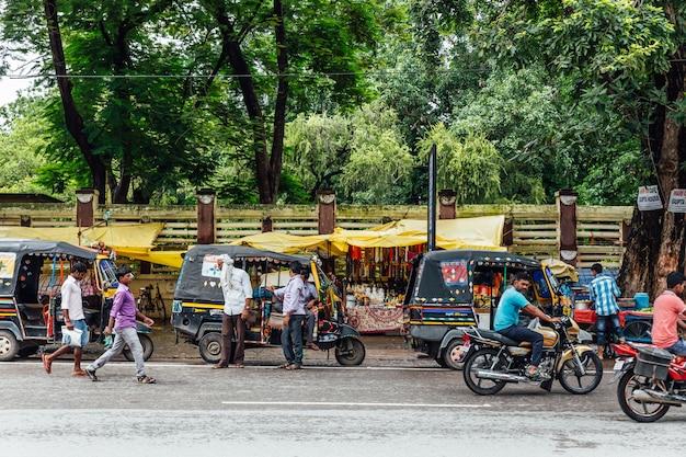 Indischer straßenmarkt mit den leuten, die motorräder und autos nahe mahabodhi-tempel bei bodh gaya, bihar, indien fahren.
