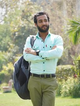 Indischer student, der am collagecampus steht - bildungskonzept