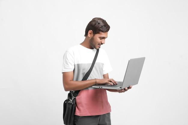 Indischer student, der laptop auf weißem hintergrund verwendet.
