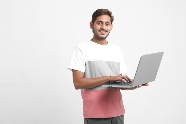 Indischer student, der laptop benutzt