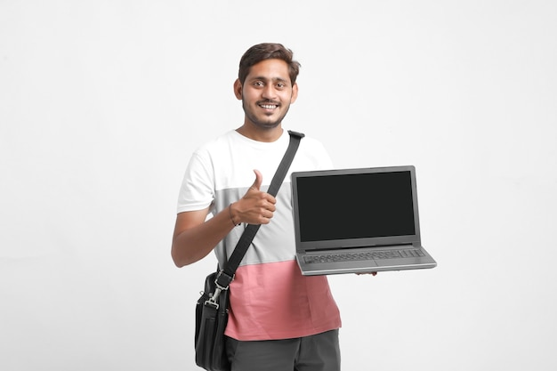 Indischer student, der laptop-bildschirm auf weißem hintergrund zeigt.
