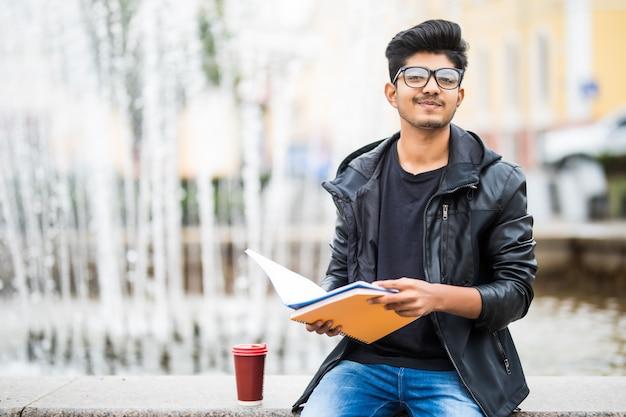 Indischer studentenmann, der einen stapel bücher hält, der nahe brunnen auf der straße sitzt