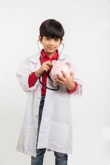 Indischer süßer junge oder kind in arztuniform mit stethoskop und untersuchendem sparschwein in der hand