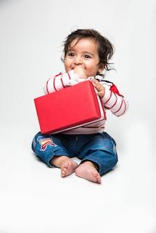 Indischer süßer kleiner junge oder säugling oder kleinkind, der mit geschenkbox auf weißem hintergrund lächelt