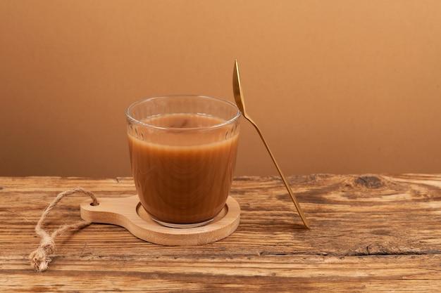 Indischer tee im glas. es wird aus stark gesüßtem schwarzen tee mit milch oder kondensmilch gebraut, oft mit ingwer und gewürzen zubereitet. beliebtes heißes getränk in indien und nepal.