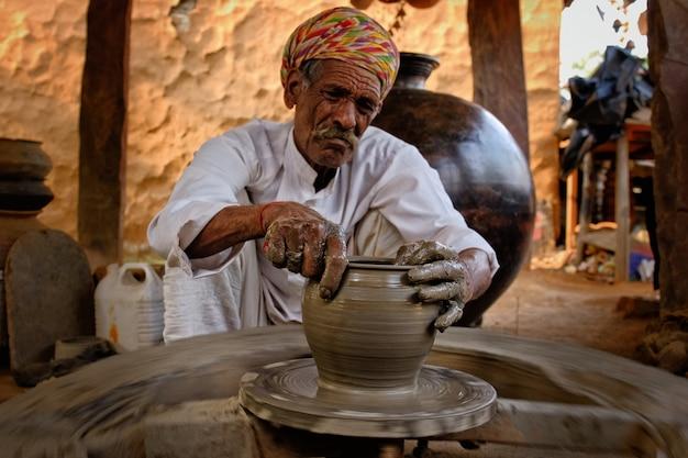 Indischer töpfer bei der arbeit. handarbeit handwerk von shilpagram, udaipur, rajasthan, indien