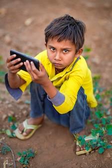 Indisches armes kind, das mit mobile am landwirtschaftsfeld spielt. ländliche szene.