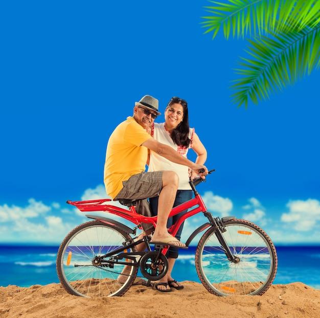 Indisches asiatisches ehepaar im ruhestand mit ihrem fahrrad oder fahrrad am strand, stimmungsvoller effekt