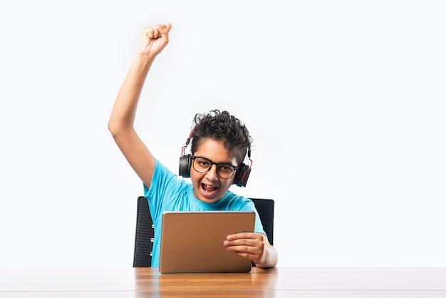 Indisches asiatisches kleines kind, das auf tablet-computer spielt oder studiert, drahtlos