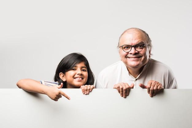 Indisches asiatisches süßes kleines mädchen, das mit opa oder großvater auf leere weiße tafel zeigt