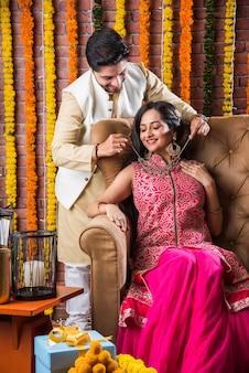Indisches attraktives paar in traditioneller kleidung feiert diwali-fest, geburtstag oder jubiläum mit überraschungsgeschenken und süßem laddoo vor dekoriertem hintergrund mit ringelblumenblüten