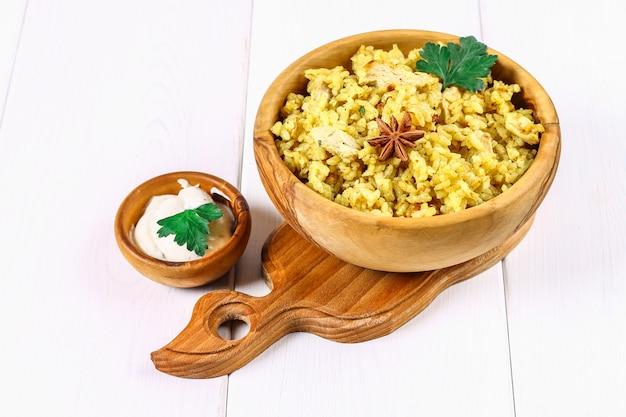 Indisches biryani mit huhn, joghurt, gewürzplatte auf einem holztisch. silvester, weihnachtsgericht.