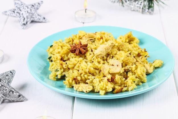 Indisches biryani mit huhn, joghurt und gewürzen in der platte auf holztisch. silvester, weihnachtsgericht