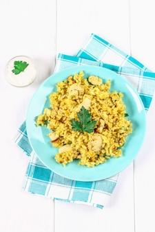 Indisches biryani mit huhn, joghurt und gewürzen in einer platte auf holztisch. neues jahr, weihnachtsgericht