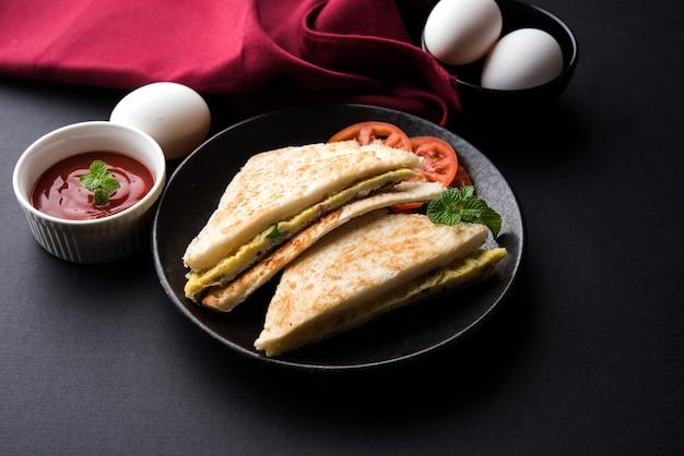 Indisches brot-omelett oder omelett-sandwich serviert mit tomatenketchup. med up von hühnerei. serviert über stimmungsvollem hintergrund. selektiver fokus