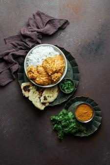 Indisches butterhuhn mit basmatireis, gewürzen, naan-brot