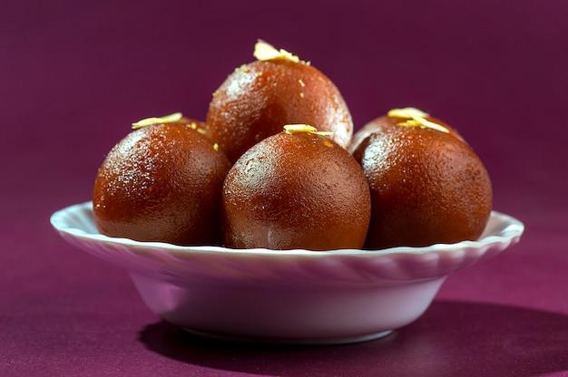 Indisches dessert: gulab jamun in weißer schüssel