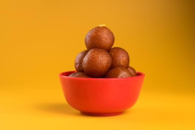 Indisches dessert oder süßes gericht: gulab jamun in der schüssel auf gelbem hintergrund.