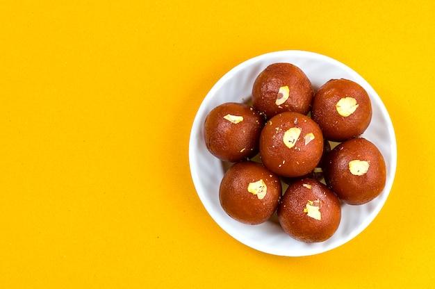 Indisches dessert oder süßes gericht: gulab jamun in der weißen schüssel auf gelbem hintergrund