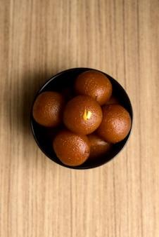 Indisches dessert oder süßes gericht: gulab jamun in einer schüssel