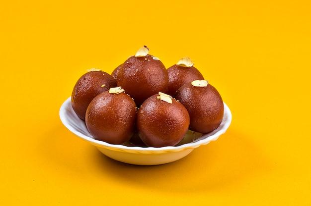Indisches dessert oder süßes gericht: gulab jamun in weißer schüssel auf gelb