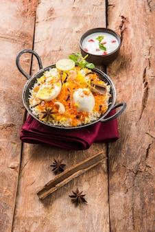 Indisches ei biryani oder anda reis serviert in kadhai oder kadai mit joghurtdip, selektiver fokus