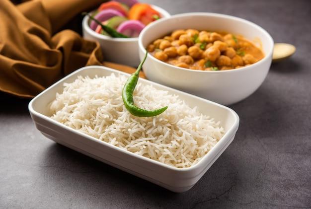Indisches essen chole chawal oder würziges kichererbsen-curry mit einfachem reis, serviert mit grünem salat. selektiver fokus