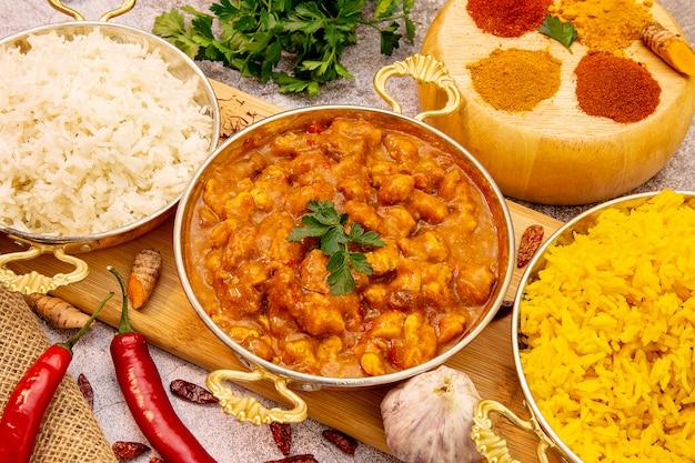 Indisches essen. curryhuhn in tomatensauce mit weißem und gelbem reis, gewürze: curry, kurkuma, heißer und milder paprika