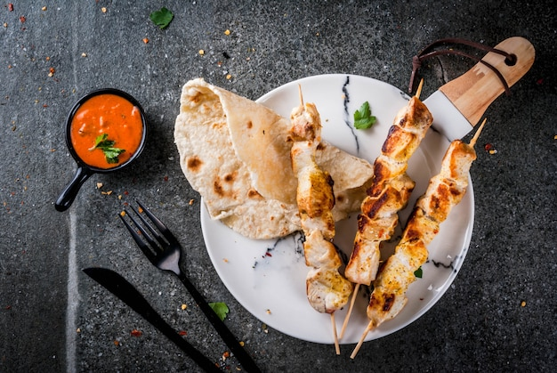 Indisches essen traditionelles gericht würziges huhn tikka masala butter hühnercurry mit indischen naan butterbrot gewürzen kräutern serviert in schüssel sauce am spieß stone dunklen tisch