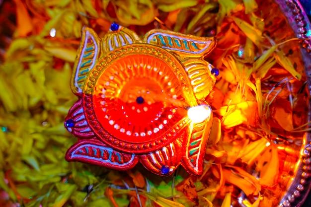 Indisches festival diwali, lampen- und ringelblumenblüten in pooja thali